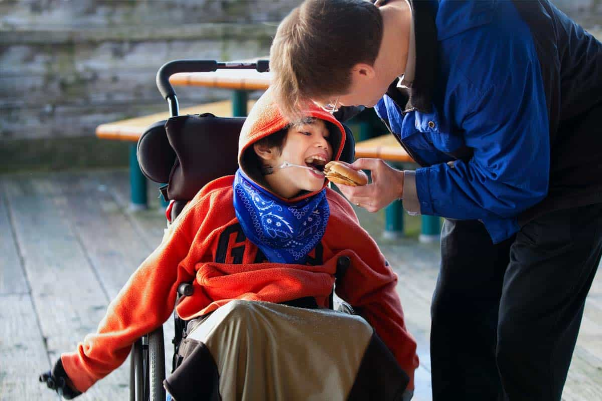 Man feeding child with cerebral palsy