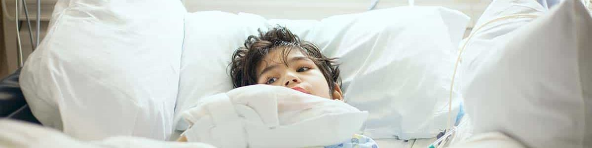 disabled boy lying sick in hospital bed